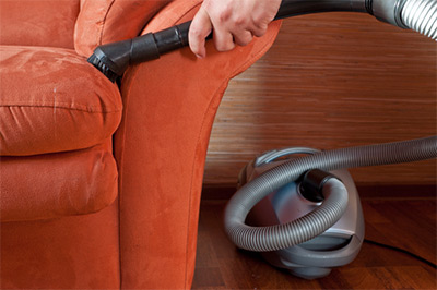 cleaning couch with an upholstery cleaner