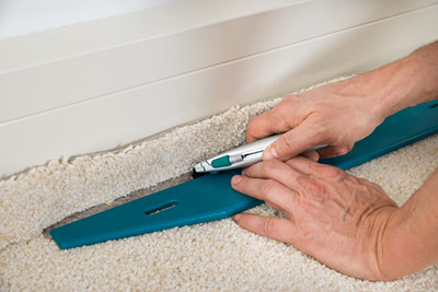 man cutting new carpet to fit
